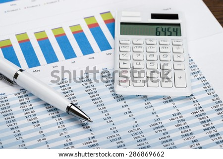 Close-up Of A Financial Data Sheet With Calculator And Ballpen - stock photo
