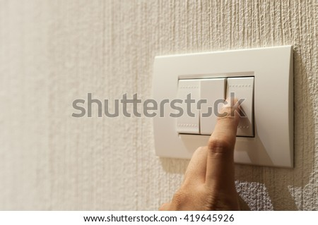 Close up of A finger is turning on a light switch on wallpaper background with copy space.