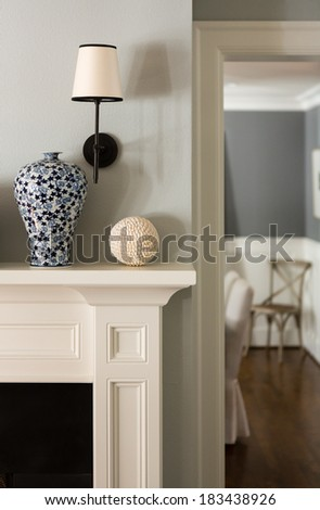 Close up of a fireplace mantle with a vase and lighting fixture. - stock photo