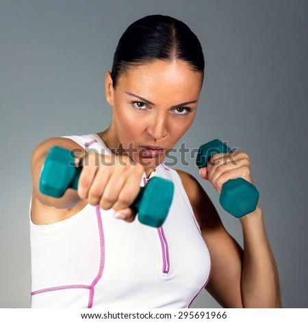Close up of a fitness woman training with dumbbells. Isolated against grey background. - stock photo