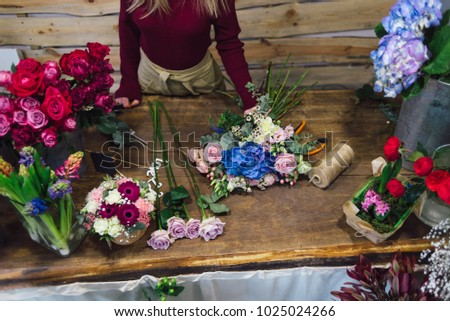 close-up of a florist's table filled with flowers and extra material near the table stands girl
