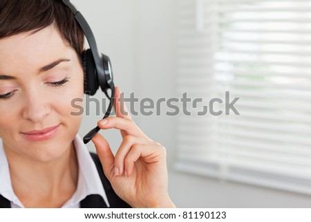 Close up of a focused secretary calling with a headset in her office - stock photo