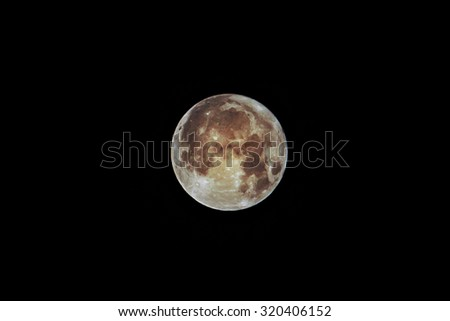 Close up of a full moon against a black background - stock photo