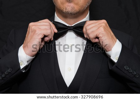 Close-up of a gentleman wearing Black Tie straightens his bowtie. - stock photo