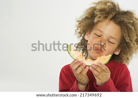 Close-up of a girl eating a slice of a melon