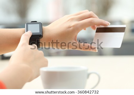 Close up of a girl hands buying on line with a credit card and a modern generic smart watch in a bar terrace - stock photo