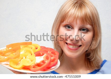 Close-up of a girl holding a dish of sliced peppers - stock photo
