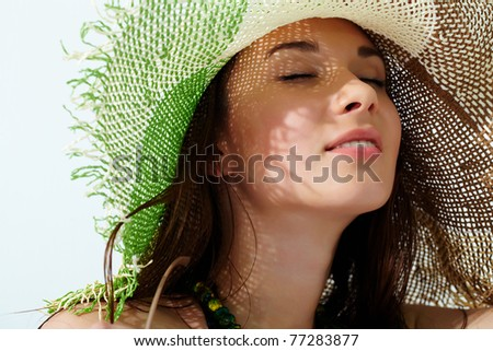 Close-up of a girl's face in straw hat enjoying the sun - stock photo