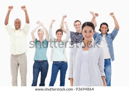 Close-up of a girl with people raising their arms in background - stock photo