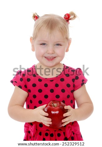 close-up of a girl with pigtails holding a big red apple.Isolated on white background, Lotus Children's Center.