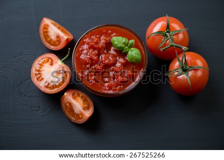 Close-up of a glass bowl with chopped tomatoes and green basil - stock photo