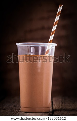 Close up of a glass of chocolate or cacao smoothie with a spiral patterned straw against a dark background