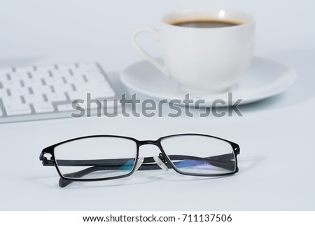 Close up of a glasses of business man with modern white keyboard and a relaxing coffee cup in white background
