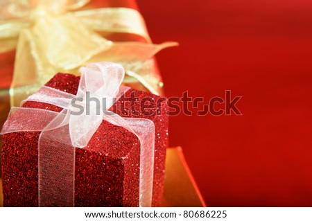Close up of a glittery red gift box with white ribbon.  Gold box and bow in the background.  Red copy space to right. - stock photo