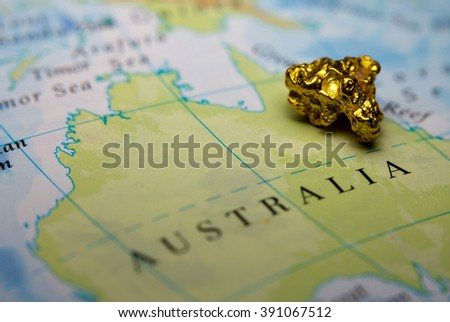 Close-up of a gold nugget on top of a map of Australia - stock photo