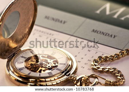 Close up of a gold pocket watch on a calendar - stock photo