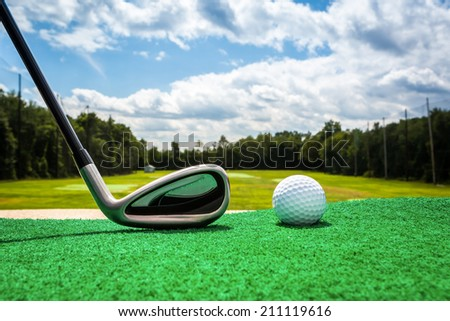 Close-up of a golf ball and a golf iron on a driving range - stock photo