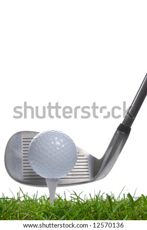 Close up of a golf ball on a tee with an iron club behind, studio shot using real grass. - stock photo