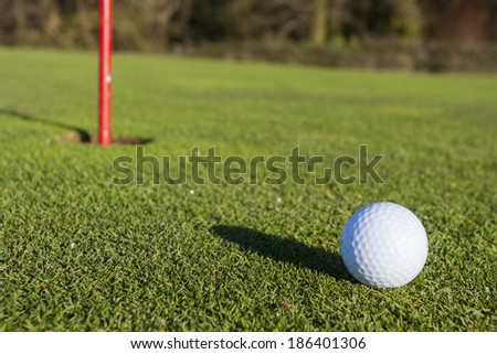 Close-up of a golf ball with the hole - stock photo