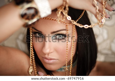 Close up of a gorgeous lady with a golden chains on her hand - stock photo