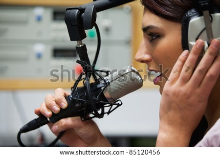 Close up of a gorgeous singer recording a track in a studio - stock photo