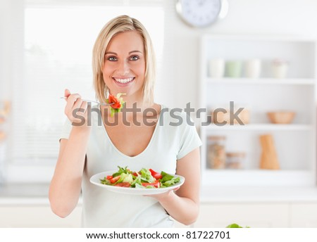 Close up of a gorgeous woman eating salad in the kitchen - stock photo