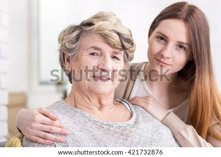 Close-up of a granddaughter holding her grandmother affectionately