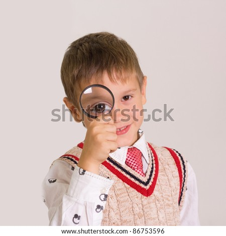 close up of a green eyed boy looking through magnifying glass - stock photo