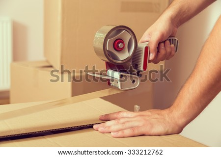 Close up of a guy's hands holding packing machine and sealing cardboard boxes with duct tape - stock photo