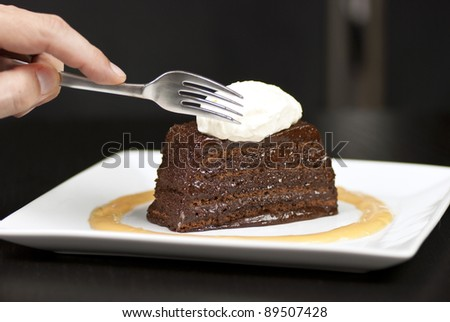 Close-up of a hand holding a fork about to slice into a chocolate marquise with a white chocolate marscapone and butterscotch sauce. - stock photo