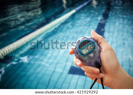 Close up of a hand holding a timer on a white background against water moving in the swimming pool - stock photo