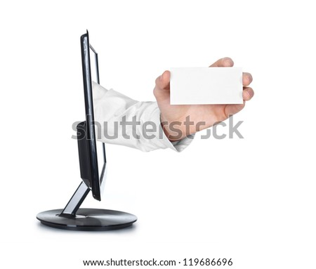 close up of a hand holding business card reaching out of a computer screen on white background.