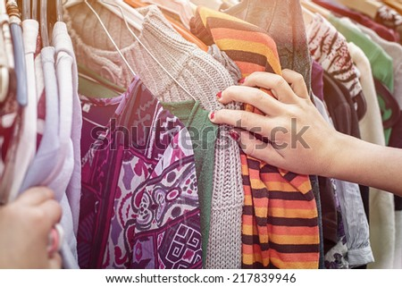 close up of a hand, looking on a flea market for clothes. - stock photo