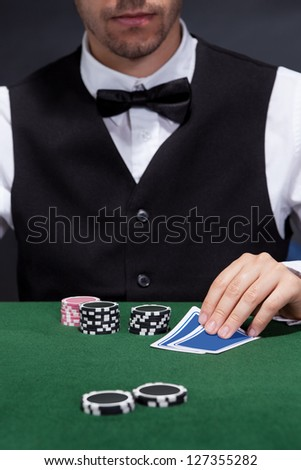 Close-up of a hand of poker player with cards and chips - stock photo