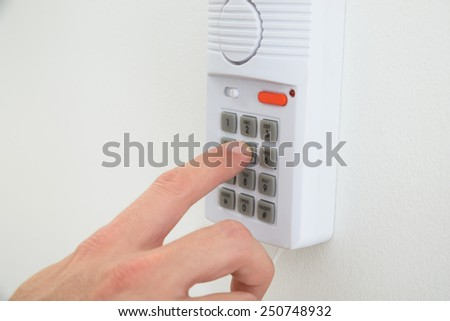 Close-up Of A Hand Pushing Button On Security System - stock photo