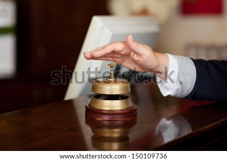 Close-up of a hand ready to press the bell at the reception of a hotel - stock photo