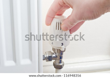 Close up of a hand turning a radiator knob either up or down.  Steel fittings and part of radiator visible, with cream painted wall and skirting board in the background. - stock photo