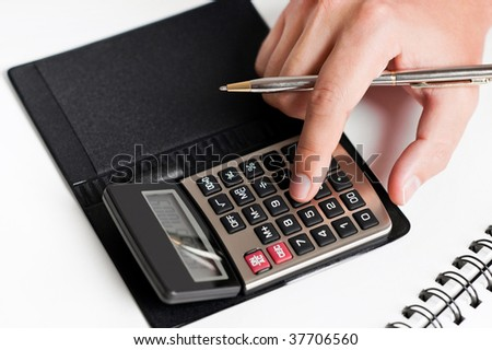 Close-up of a hand typing on calculator with a white background - stock photo
