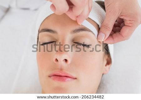 Close up of a hand waxing beautiful woman's eyebrow - stock photo