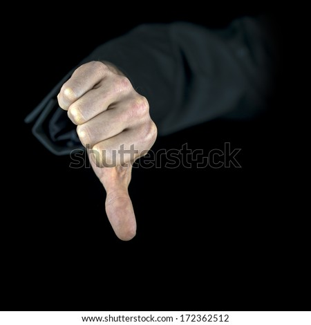 Close-up of a hand with black sleeve showing the thumb down, gesture of disapproval, isolated on black background - stock photo