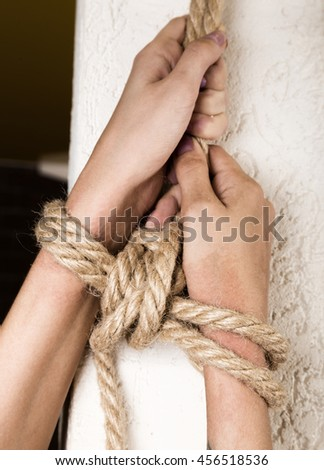 Close-up of a Hands kidnapped, victim woman tied up with rope in emotional stress and pain. model tied up with fetish restraint rope. - stock photo