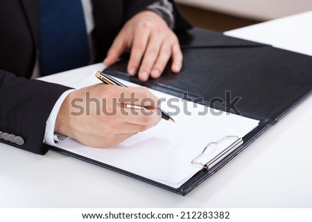 Close-up of a hands of businessman writing on clipboard