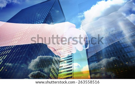 Close up of a handshake against low angle view of skyscrapers at sunset - stock photo