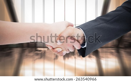Close up of a handshake against room with large window looking on city