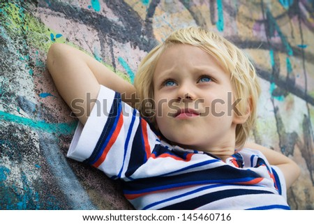 Close-up of a handsome boy in deep thought leaning against a graffiti wall - stock photo