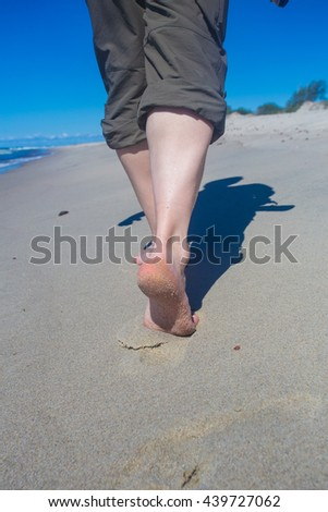 Close-up of a handsome man walking  along the beach. Barefoot male legs walk on the shoreline. Photo camera. - stock photo