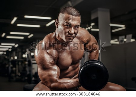 Close Up of a handsome power athletic man bodybuilder doing exercises with dumbbell. Fitness muscular body on dark background. Muscle athlete man in gym making elevations. Bodybuilder training in gym. - stock photo
