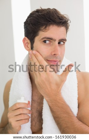 Close up of a handsome young man applying moisturizer on his face - stock photo