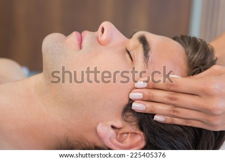Close up of a handsome young man receiving head massage at spa center - stock photo