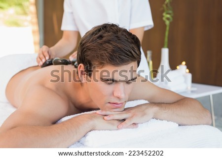 Close up of a handsome young man receiving stone massage at spa center